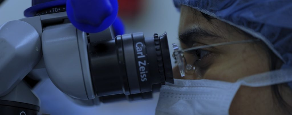 Doctor looking through microscope in development of innovative medical technologies